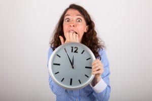 Die junge Geschäftsfrau hält eine große Uhr in den Händen